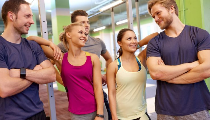 group of happy people at gym