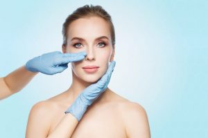 The surgeon evaluates the patient's facial structure before doing the surgical procedure.